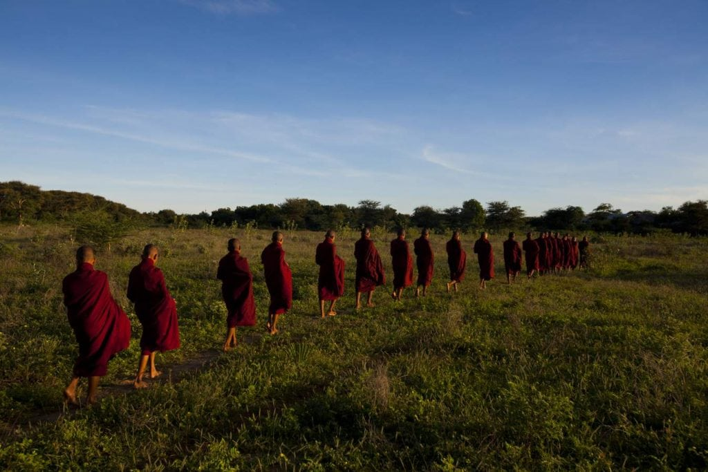 Monks in procession at dawn to collect alms, Bagan, Myanmar